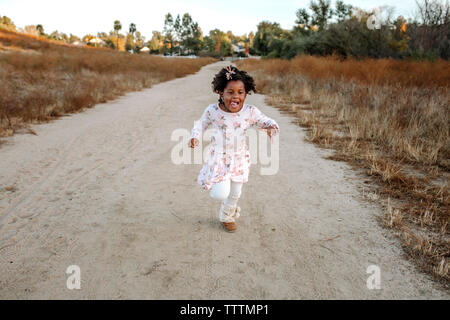 Playful girl running on dirt road in forest Banque D'Images