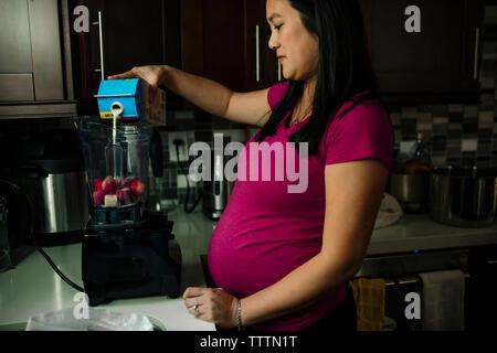 Pregnant woman pouring milk dans blender smoothie fraise pendant la préparation à la maison Banque D'Images