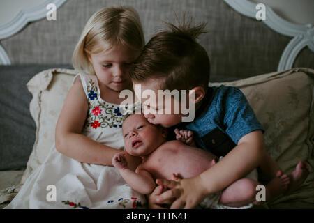 Frères et sœurs avec mignon nouveau-né soeur assis sur le lit à la maison Banque D'Images