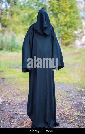 Un homme de grande taille dans un costume sombre avec une capuche se trouve dans la forêt sur un fond vert. La photographie verticale Banque D'Images