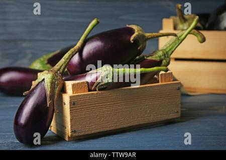 Les aubergines fraîches dans la caisse sur fond de bois Banque D'Images