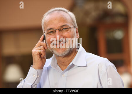 Old Indian man talking on a mobile phone Banque D'Images