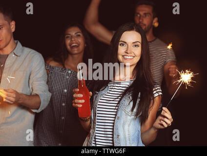 Happy friends avec cierges sur beach party Banque D'Images