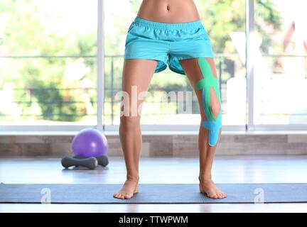 Femme avec bandage élastique genou sur faire du sport les cours d'exercice physique Banque D'Images