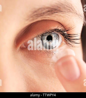 Close up of young woman putting contact lens dans son œil