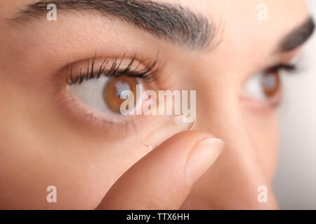 Jeune femme mettant en lentilles de contact l'œil, vue en gros plan. Médecine et concept vision