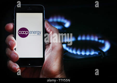 Un homme à la recherche sur le site web logo pour société de l'énergie Énergie Coop sur son téléphone devant sa cuisinière à gaz (usage éditorial uniquement) Banque D'Images