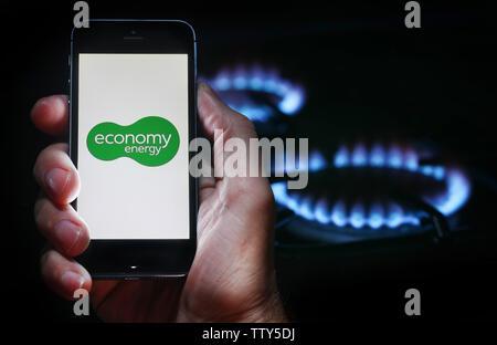 Un homme à la recherche sur le site web logo pour entreprise de l'énergie Énergie Économie sur son téléphone devant sa cuisinière à gaz (usage éditorial uniquement) Banque D'Images