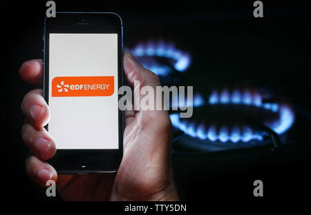 Un homme à la recherche sur le site web logo pour société d'énergie de l'énergie EDF sur son téléphone devant sa cuisinière à gaz (usage éditorial uniquement) Banque D'Images