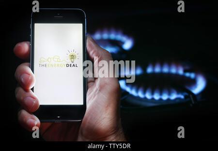 Un homme à la recherche sur le site web logo pour société de l'énergie l'Accord énergétique sur son téléphone devant sa cuisinière à gaz (usage éditorial uniquement) Banque D'Images
