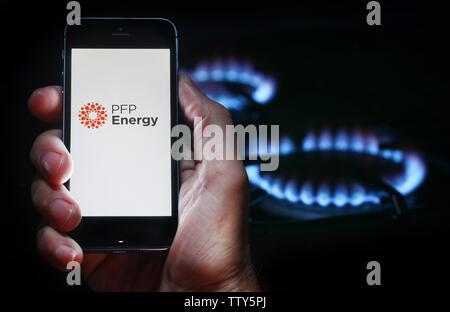 Un homme à la recherche sur le site web logo pour société d'énergie de l'énergie du PPP sur son téléphone devant sa cuisinière à gaz (usage éditorial uniquement) Banque D'Images