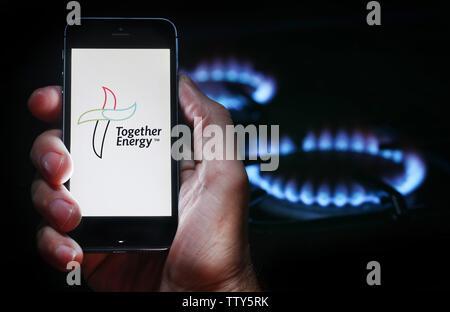 Un homme à la recherche sur le site web logo pour société d'énergie de l'énergie ensemble sur son téléphone devant sa cuisinière à gaz (usage éditorial uniquement) Banque D'Images
