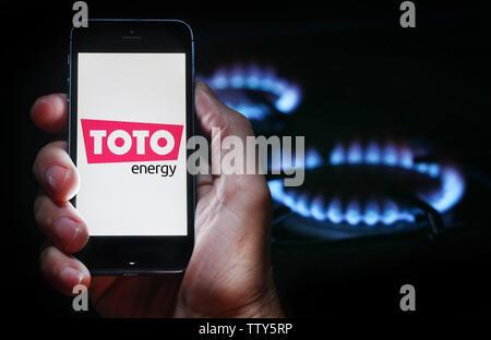 Un homme à la recherche sur le site web logo pour société de l'énergie Énergie Toto sur son téléphone devant sa cuisinière à gaz (usage éditorial uniquement) Banque D'Images