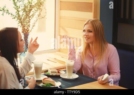 Belles jeunes femmes se reposant dans cafe Banque D'Images