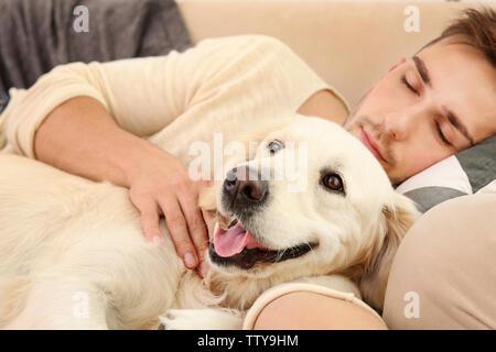 Bel homme avec mignon chien dormir dans un canapé Banque D'Images