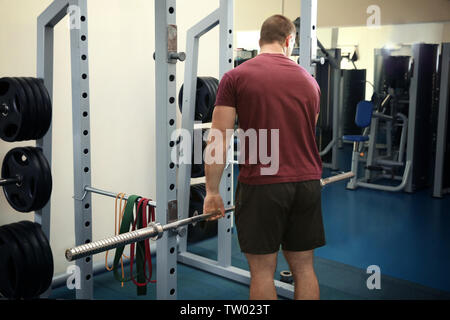 Young handsome man with barbell training in gym Banque D'Images
