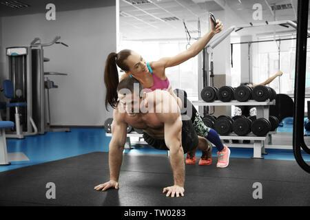 Jeune homme faisant pousser ups tout en prenant femme sport en selfies Banque D'Images