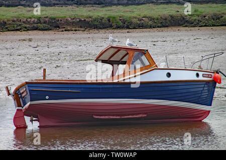 SEATON, Devon, Angleterre - 22 MAI 2012: un petit bateau de pêche se trouve sur le côté à marée basse sur le fleuve Ax estuaire. Deux mouettes sont perchées sur le ca Banque D'Images
