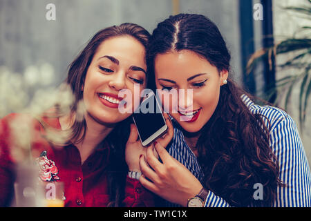 Happy young woman having a phone call alors que son meilleur ami à l'écoute sa conversation.