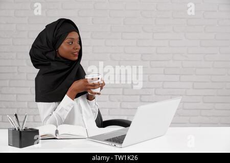 Beau, charmant muslim woman sitting at table in office, holding white Cup, la pensée. Jolie dame d'affaires de l'Afrique noire à porter le hijab et les vêtements blancs à la route.