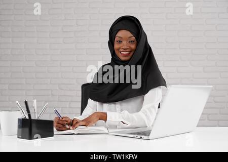 Belle et élégante femme musulmane africaine portant en noir hijab posant sur le lieu de travail, à la recherche à l'appareil photo. Female office worker sitting at table et travailler à l'ordinateur portable ordinateur portable, dans l'écriture.