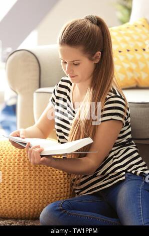 Jolie jeune fille assise sur le plancher à la maison Banque D'Images