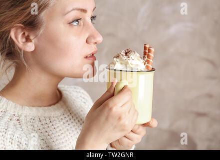 Woman holding metal tasse et dégustant une délicieuse boisson au cacao avec crème fouettée, Close up Banque D'Images