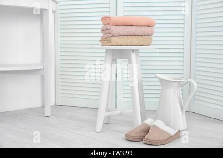 Belle composition avec des serviettes, des chaussons et verseuse en lumière prix Banque D'Images