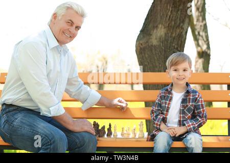 Adorable petit garçon avec son grand-père jouer aux échecs sur un banc de parc au printemps Banque D'Images