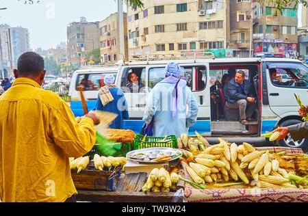 Le CAIRE, ÉGYPTE - Le 22 décembre 2017: Le stand de vendeur de maïs frais, situé à la route, avec une vue sur le trafic chaotique et de monde dans les bus micro Al Sayed Banque D'Images