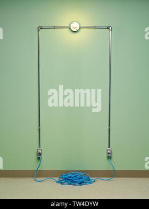 Incompétent et dangereux du circuit électrique avec rallonge spirale bleu branché sur deux AC prises murales aux ampoules à incandescence sur le mur vert Banque D'Images