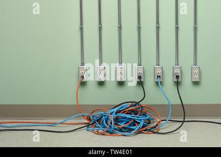 Bleu, orange et noir tangled rallonges branchées sur rangée de prises électriques AC sur mur vert. Banque D'Images