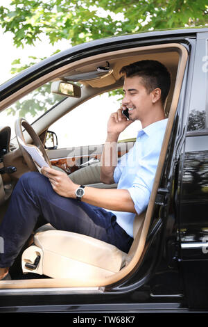 Young businessman talking on phone in car Banque D'Images