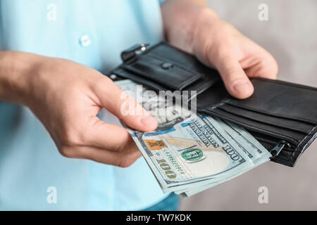 Woman holding wallet with dollar bills