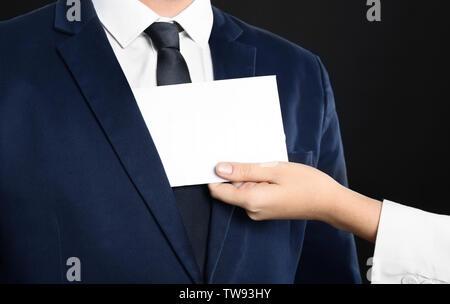 Woman putting enveloppe avec pot-de-vin dans la poche de l'homme, gros plan Banque D'Images