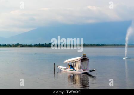 Une maison ou bateau bateau Shikara sur le lac Dal à Srinagar, Jammu-et-Cachemire, en Inde. Le Grand Himalaya gamme sont visibles à une distance. Image prise en Banque D'Images
