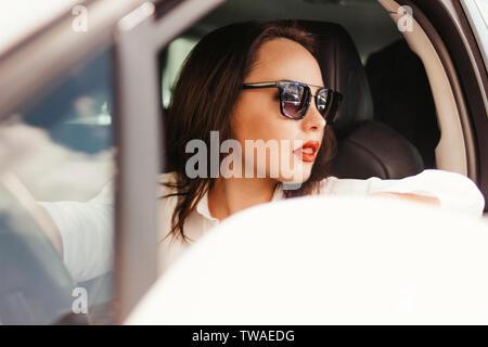 Belle jeune femme brune élégante réussie avec lèvres rouges dans la voiture conduite lunettes
