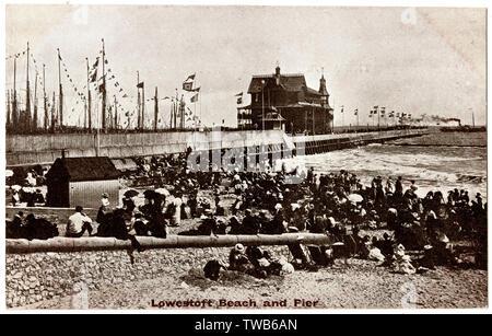 Les vacanciers sur la plage, avec l'embarcadère à l'arrière-plan, Lowestoft, Suffolk. Date: vers 1910