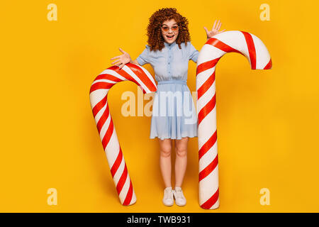 Rousse frisée woman standing with positive big sweet Candy Cane sur fond jaune Banque D'Images