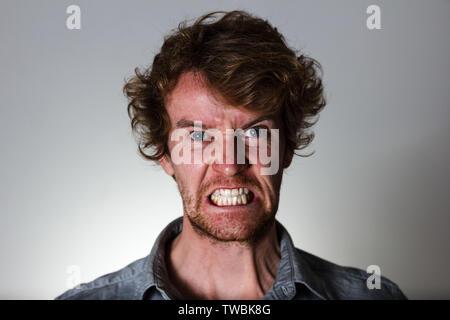 Jeune homme en colère sur fond gris Banque D'Images