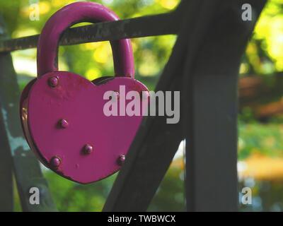 Old rusty en forme de coeur rose sur un pont en acier cadenas, gros plan, arrière-plan conceptuel de l'amour Banque D'Images