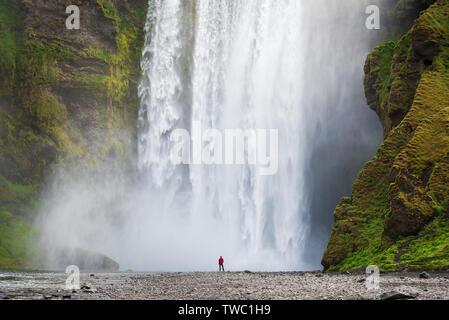 Un touriste à la veste rouge ressemble à une énorme cascade Skogafoss. Une célèbre attraction touristique de l'Islande Banque D'Images