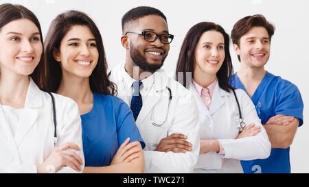 Le personnel médical heureux ensemble permanent en clinique, posant avec bras croisés Banque D'Images
