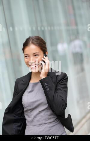 Business Woman talking on smart phone smiling happy balade en extérieur. Les jeunes portrait asiatique multiraciale avoir conversation sur mobile smartphone La ville de New York, Manhattan, USA. Banque D'Images