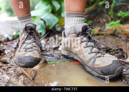 Chaussures de randonnée randonneur sur dans l'eau flaque en forêt tropicale. Randonnée Les randonneurs en bottes homme libre. Les pieds mâles. Banque D'Images