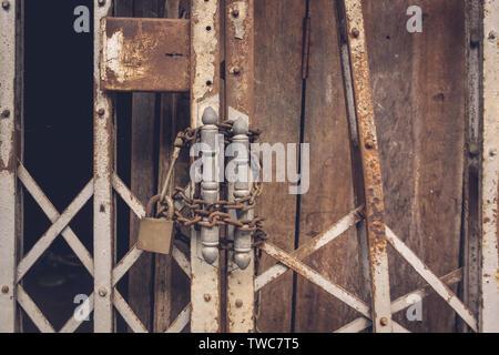 La vue de face, vieil or et de verrouillage en acier endommagé et acier rouillé sur fond de porte porte en bois Banque D'Images