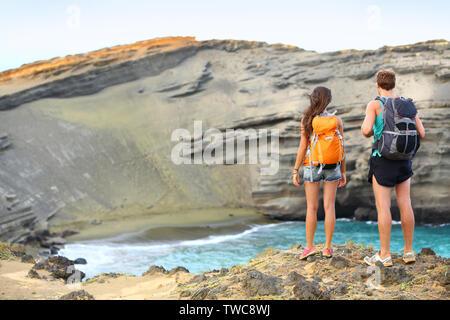 Les randonneurs - couple voyage touristes randonnée sur Hawaii. Balades touristiques backpackers sur plage de sable vert, Papakolea sur Big Island, Hawaii, USA. Young happy couple voyageant avec sac à dos. Banque D'Images