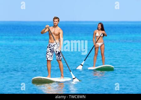 Paddleboard plage gens sur stand up paddle board surf surf en mer océan sur Big Island, Hawaii belles jeunes multi-ethnic couple, mixed race woman and Caucasian man faisant du sport de l'eau. Banque D'Images