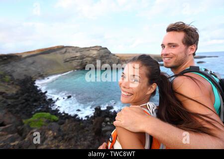 Randonnées - voyages touristiques couple sur Hawaii randonnée. Balades touristiques backpackers sur plage de sable vert, Papakolea sur Big Island, Hawaii, USA. L'Interracial young happy couple voyageant avec sac à dos. Banque D'Images