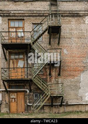 Old rusty fire escape sur un bâtiment industriel abandonné Banque D'Images